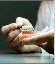 dental tech examines a partial dental bridge for quality
