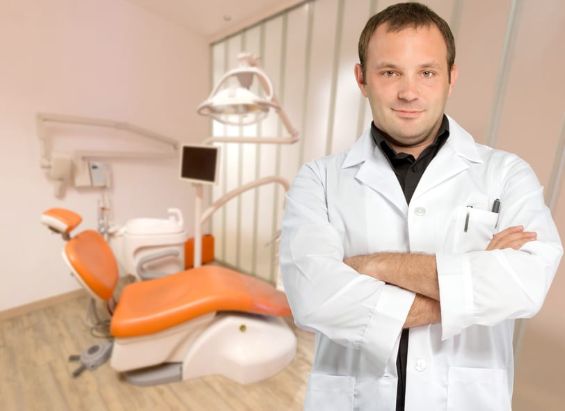 A male dentist standing with his arms crossed and an orange treatment chair in the background