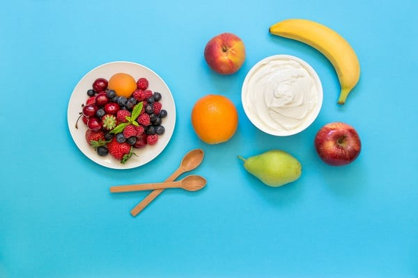 A plate of berries, bowl of yogurt, two spoons and other fruit on a light blue background