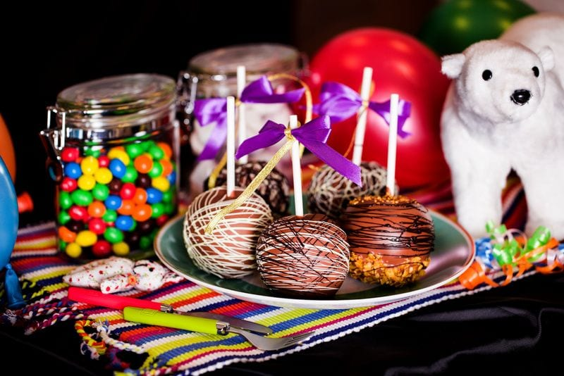 A table with cakepops on a plate and jars of candy in the background