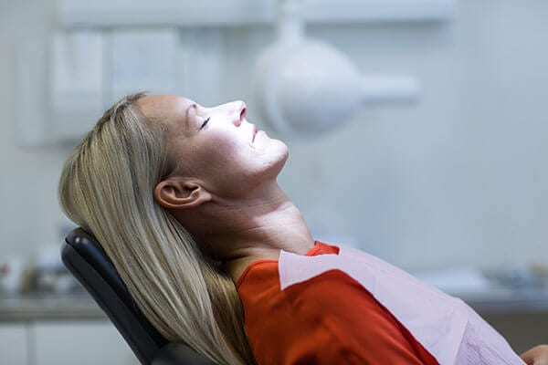 Woman with blonde hair laying back in dental chair