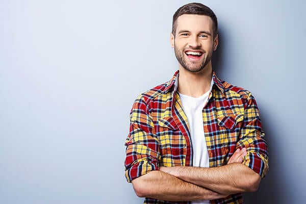 A smiling man in a red, yellow, and orange plaid shirt standing against a light blue background