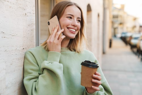 young woman smiling outdoors while talking on the phone and holding a coffee cup